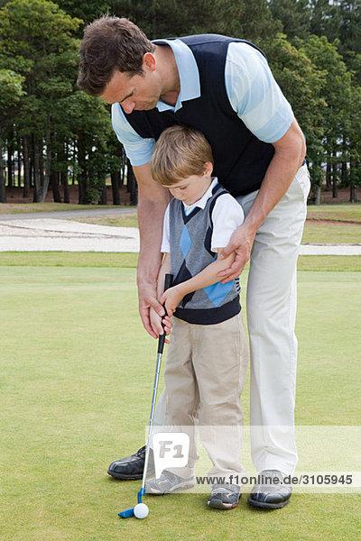 Vater unterrichtet seinen Sohn Golf