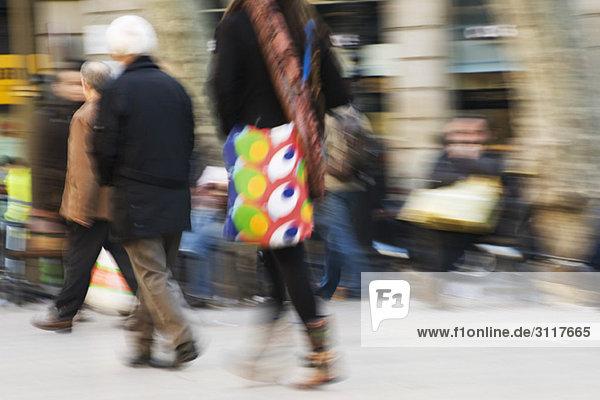Pedestrians walking on sidewalk  blurred