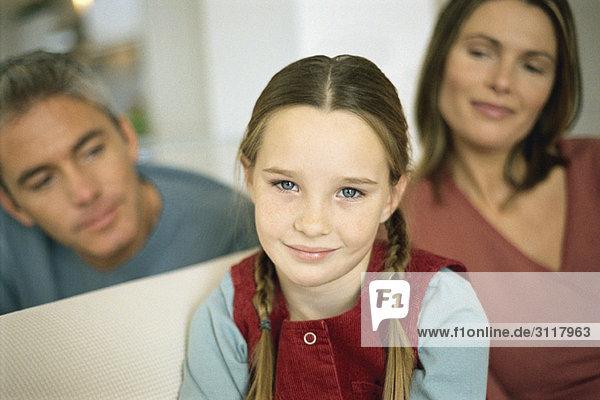 Kleines Mädchen lächelt in die Kamera  Eltern im Hintergrund