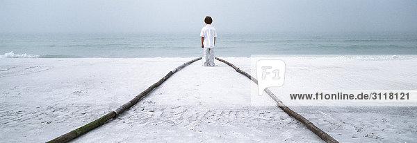 Junge steht am Ende des Fußweges am Strand und schaut auf das Meer. Junge steht am Ende des Fußweges am Strand und schaut auf das Meer.