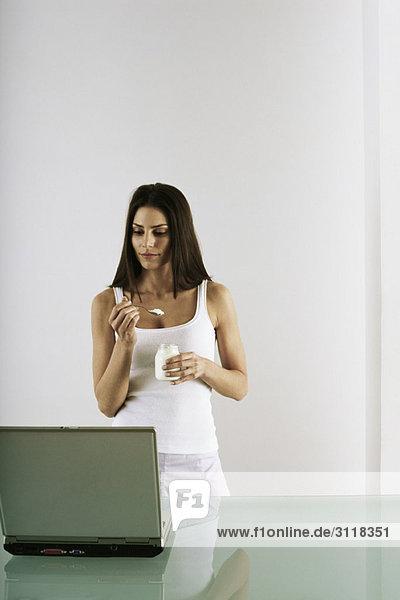 Frau in der Pause essen Snack  Blick auf Laptop-Computer
