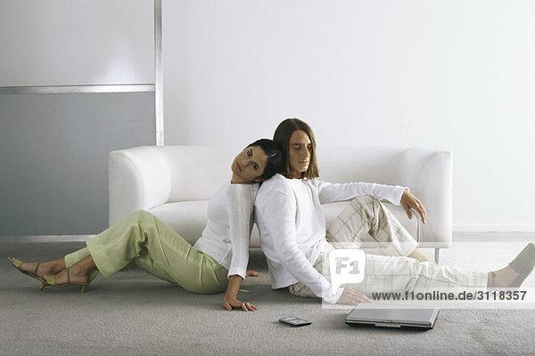 Paar sitzt Rücken an Rücken auf dem Boden