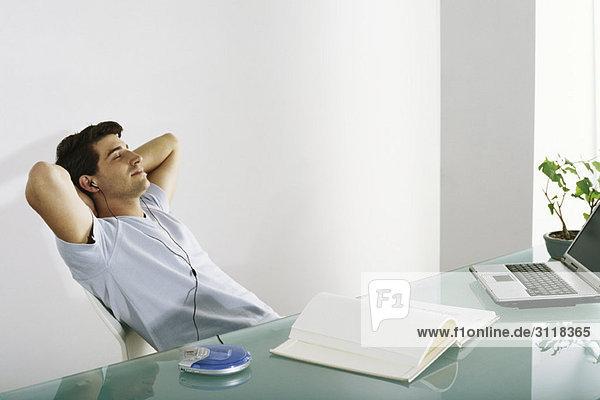 Mann am Schreibtisch lehnt sich mit den Händen hinter dem Kopf zurück und hört Kopfhörer.