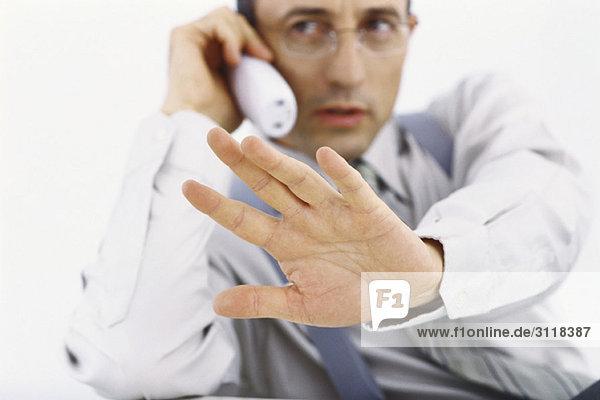 Geschäftsmann am Telefon  der mit der Hand die Geste stoppt.