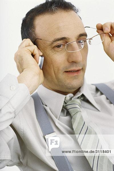 Geschäftsmann mit dem Handy  der die Brille abnimmt