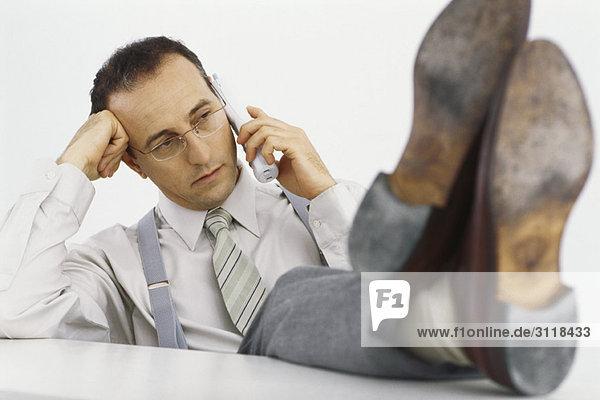 Geschäftsmann am Telefon mit erhobenen Füßen auf dem Schreibtisch