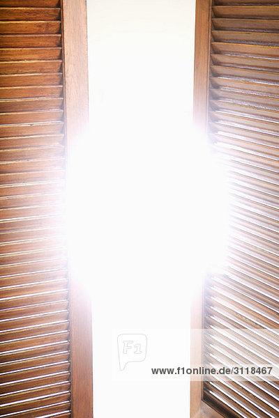 Holzfensterläden teilweise geöffnet für helles Sonnenlicht Holzfensterläden teilweise geöffnet für helles Sonnenlicht