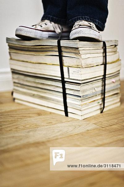 Person  die auf dem gebundenen Stapel von Büchern und Zeitschriften steht. Person, die auf dem gebundenen Stapel von Büchern und Zeitschriften steht.