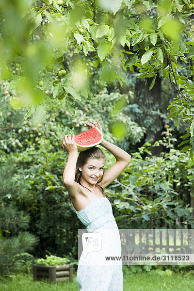 young woman with watermelon in garden