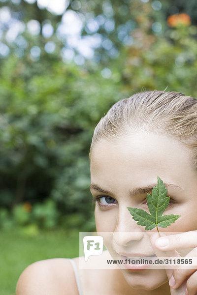 Young Frau blickt auf leaf