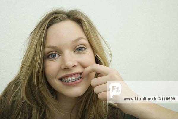 Teenagermädchen mit Zahnspange und Fingerspitze