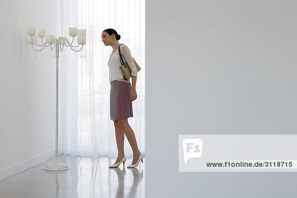 Frau schaut auf kunstvolle Kandelaber  volle Länge