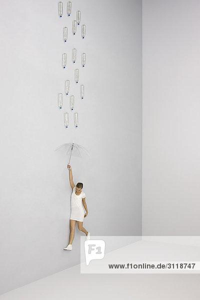 Frau in der Luft hält Regenschirm unter regnerischen Wasserflaschen