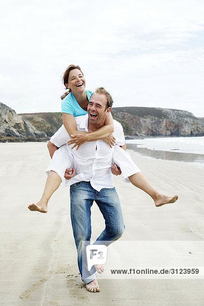 Mann trägt eine Frau huckepack am Strand  Frontal