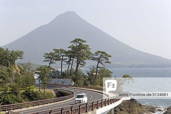 Auto auf einer Küstenstraße  Vulkan im Hintergrund  Ibusuki  Kyushu  Japan