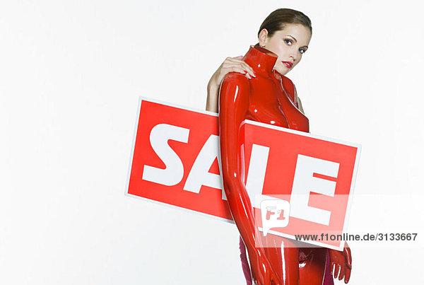Frau mit Schaufensterpuppe und Verkaufsschild
