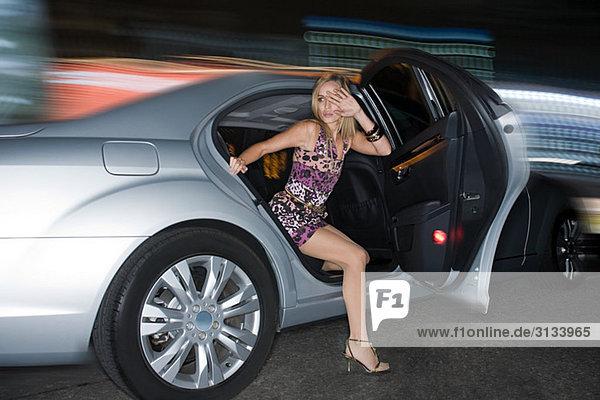 Junge Frau beim Aussteigen aus dem Auto