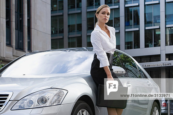 Geschäftsfrau  die sich auf ein Auto stützt