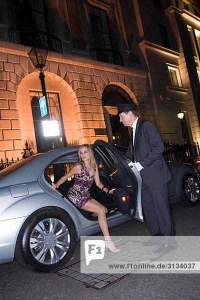 Reiche Frau steigt aus dem Auto aus