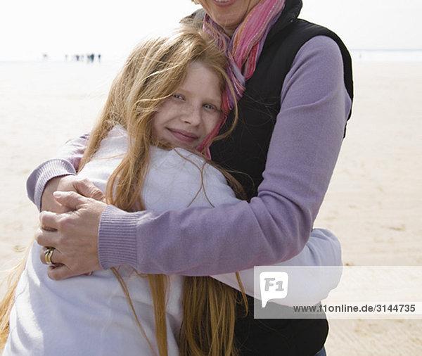 Frau umarmt Mädchen am Strand