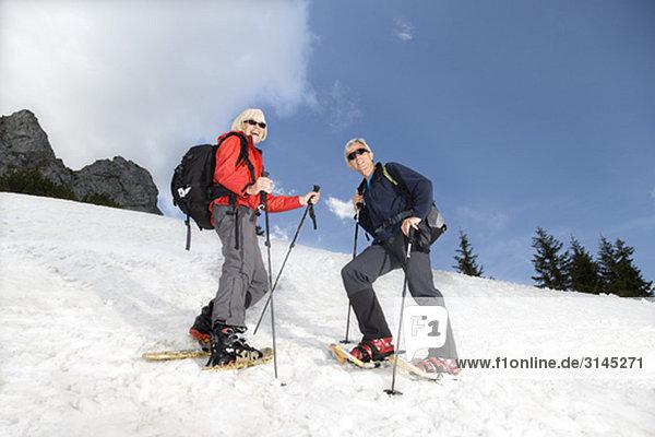 Seniorenpaar Schneeschuhwandern in den Bergen