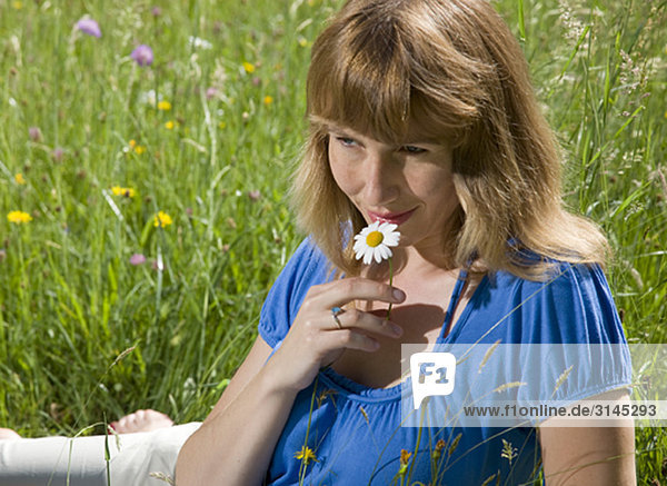 Frau im Gras liegend mit Frühlingsblumen