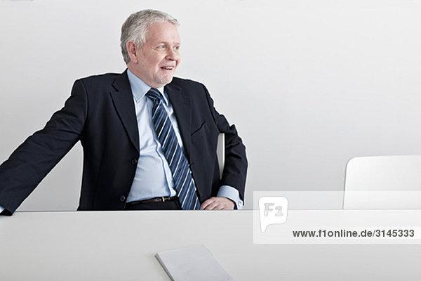 Mann sitzend  lächelnd am Schreibtisch