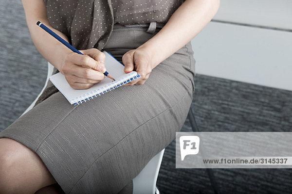 Frau schreibt auf Notizblock