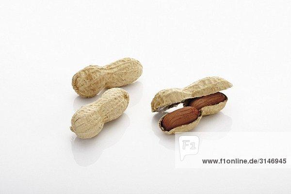Drei Erdnüsse  eine geöffnet