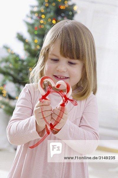 Kleines Mädchen hält Herz aus Zuckerstangen