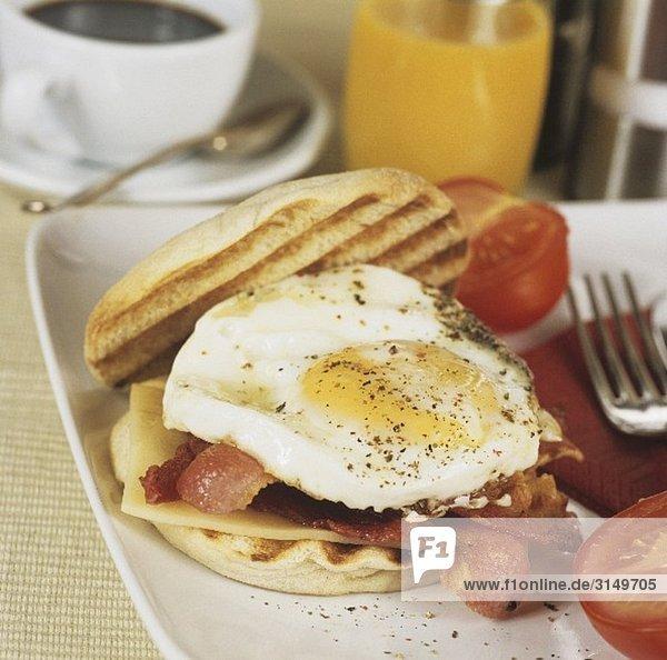 Brötchen mit Spiegelei  Bacon  Käse und Tomaten zum Frühstück