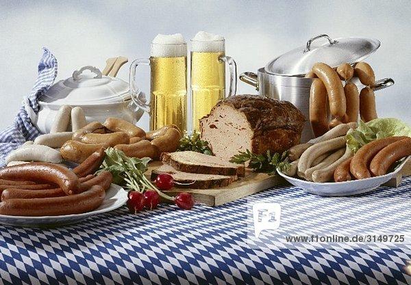 Bayerische Wurstspezialitäten mit Bier auf Tischdecke