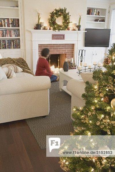Frau am Kamin im weihnachtlich dekorierten Wohnzimmer