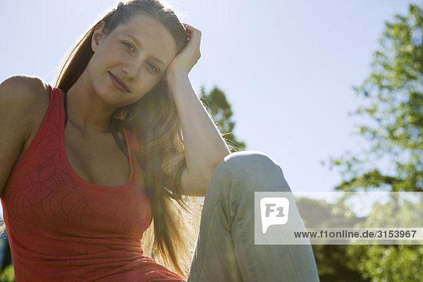 Junge Frau im Freien auf sonnigen Tag  Lächeln  Portrait sitzend