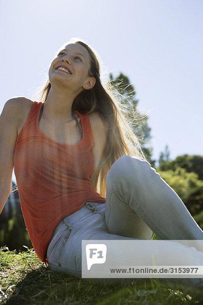 Junge Frau an sonnigen Tag im Freien sitzen  Nachschlagen und lächelnd