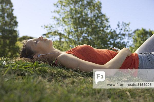 Junge Frau auf Boden anhören von MP3-Player  Augen geschlossen