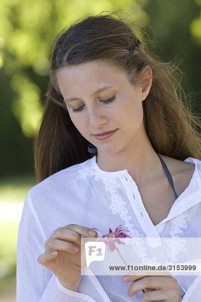 Junge Frau Rupfen aus Flower petals