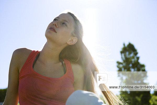Junge Frau im Freien sitzen  Blick nach oben