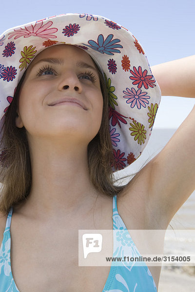 Young woman wearing sun hat at beach  looking up  smiling  portrait