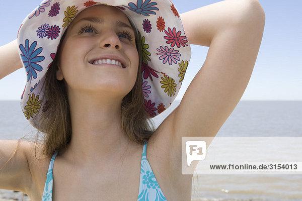 Frau tragen Sunhat am Strand  Nachschlagen und lächelnd