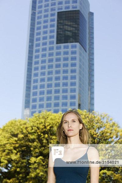 Frau im Tank Top Wegsehen  Hochhaus Gebäude im Hintergrund