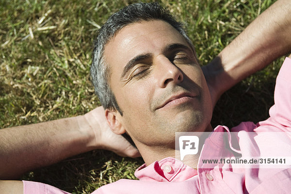 Mann auf Gras liegend mit Hände hinter Kopf und Augen geschlossen