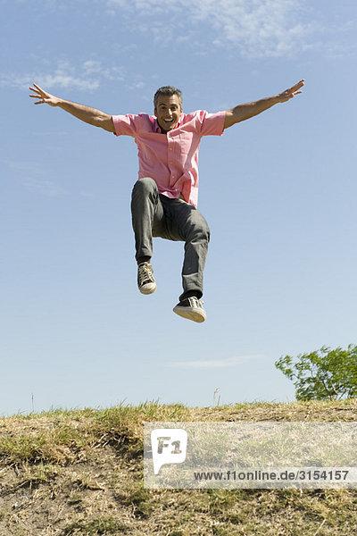 Aufgeregt Mann mit Arme in die Luft springen