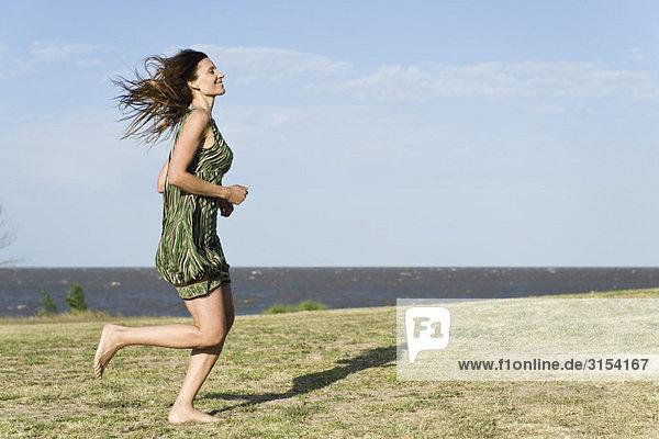 Frau in Kleid quer durch Gras  barfuss