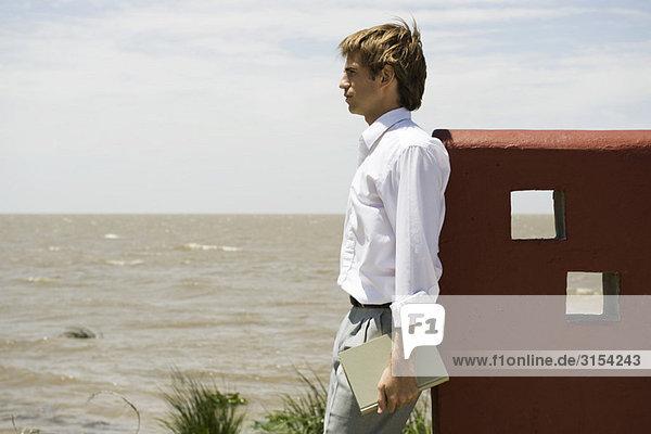 Man Standing in der Nähe von Wasserrand betrachten Blick contemplatively