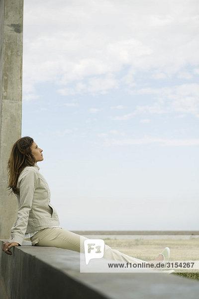 Frau sitzt auf einem Felsvorsprung betrachten Blick  Tagträumen