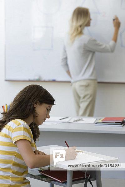 Gymnasiast macht sich Notizen als Lehrer schreibt auf Whiteboard