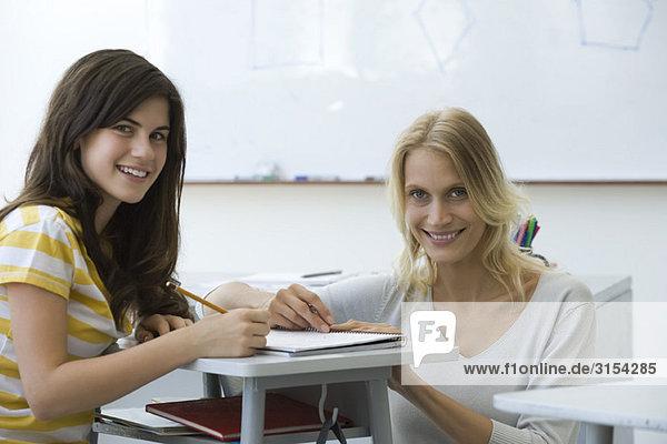 Lehrer assistiert Schüler  beide lächelnd vor der Kamera