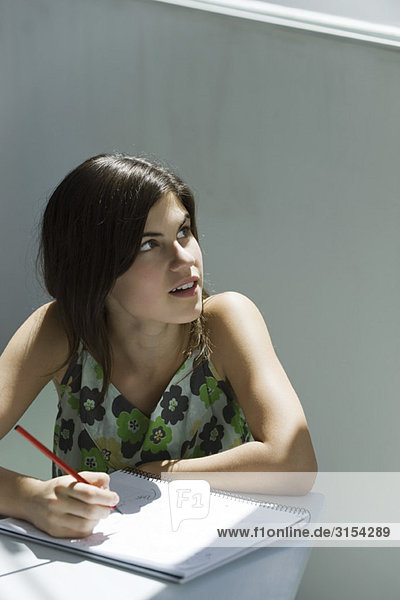 Teenagermädchen mit Stift und Notizbuch  Blick über die Schulter aus dem Fenster
