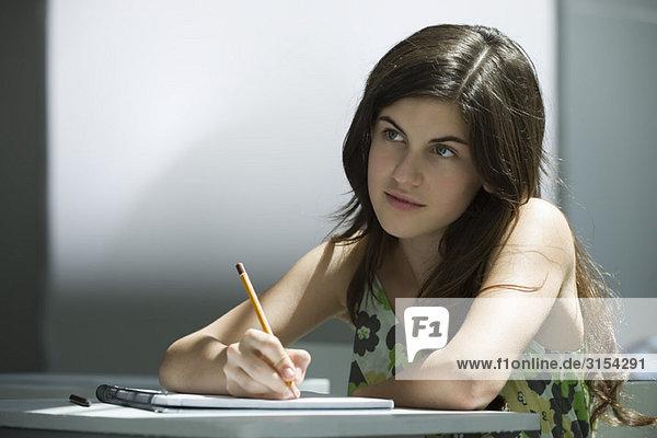 Teenager-Mädchen beim Schreiben im Notizbuch  nachdenklich wegschauen